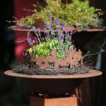 Conus mit Schale und Blumenkranz